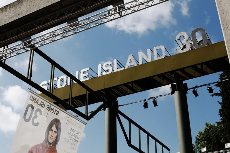 STONE ISLAND 30 billboard against blue sky with photo banner below it