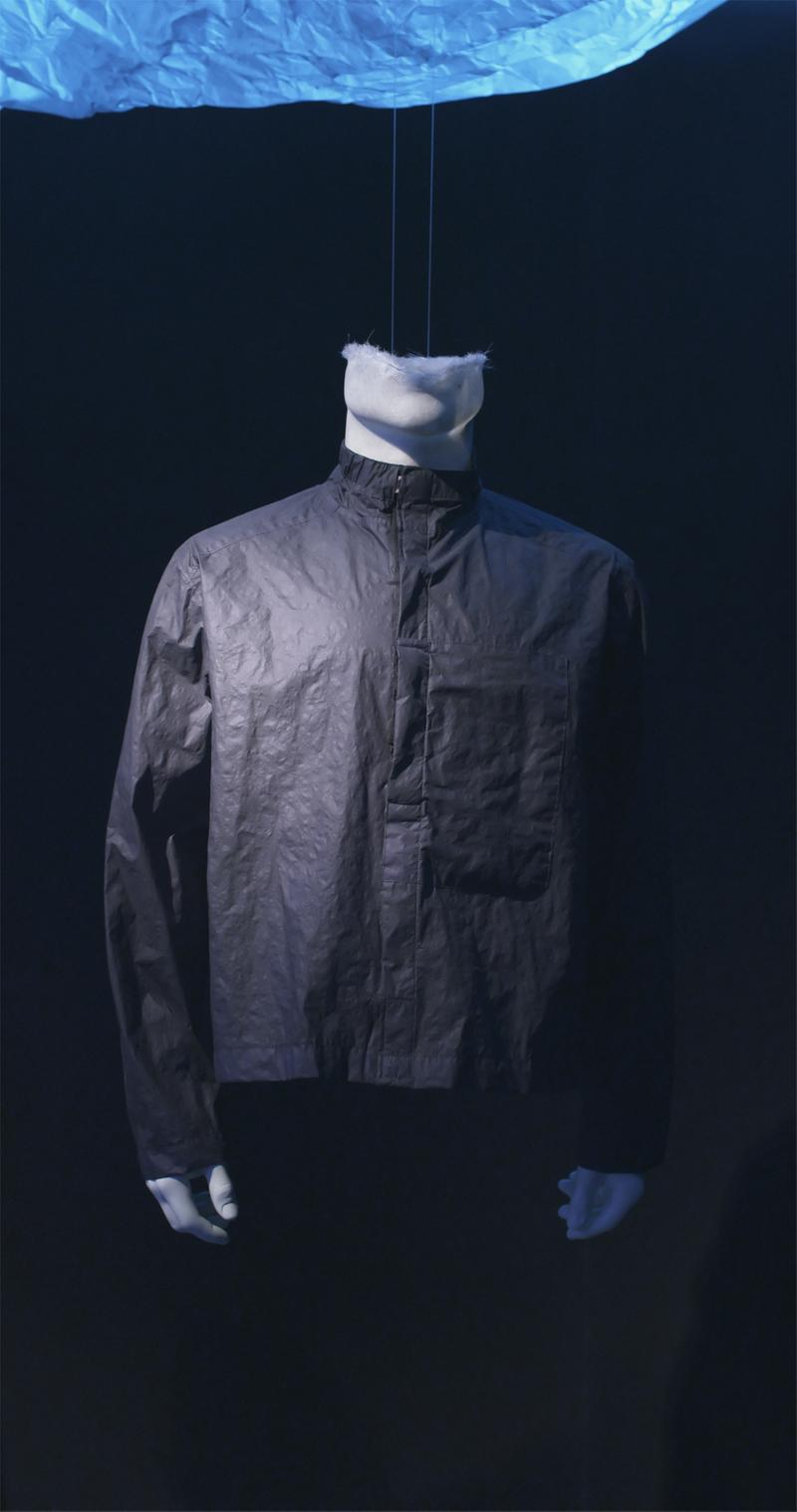 Dark colored jacket with high tab collar displayed on mannequin bust