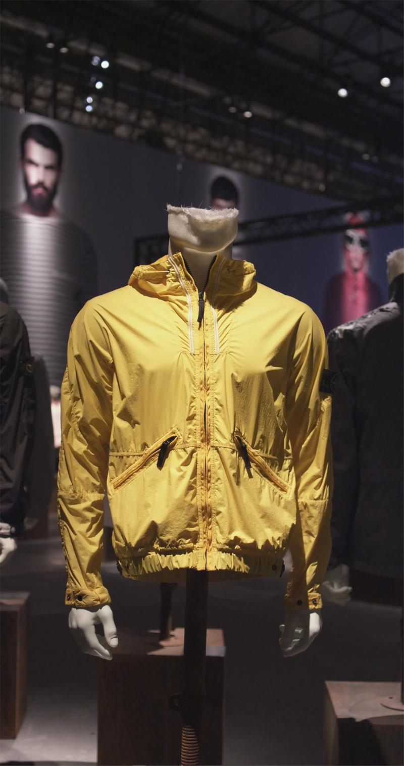 Yellow hooded jacket displayed on mannequin bust with zipper down the front, zippered pockets and elasticated hem