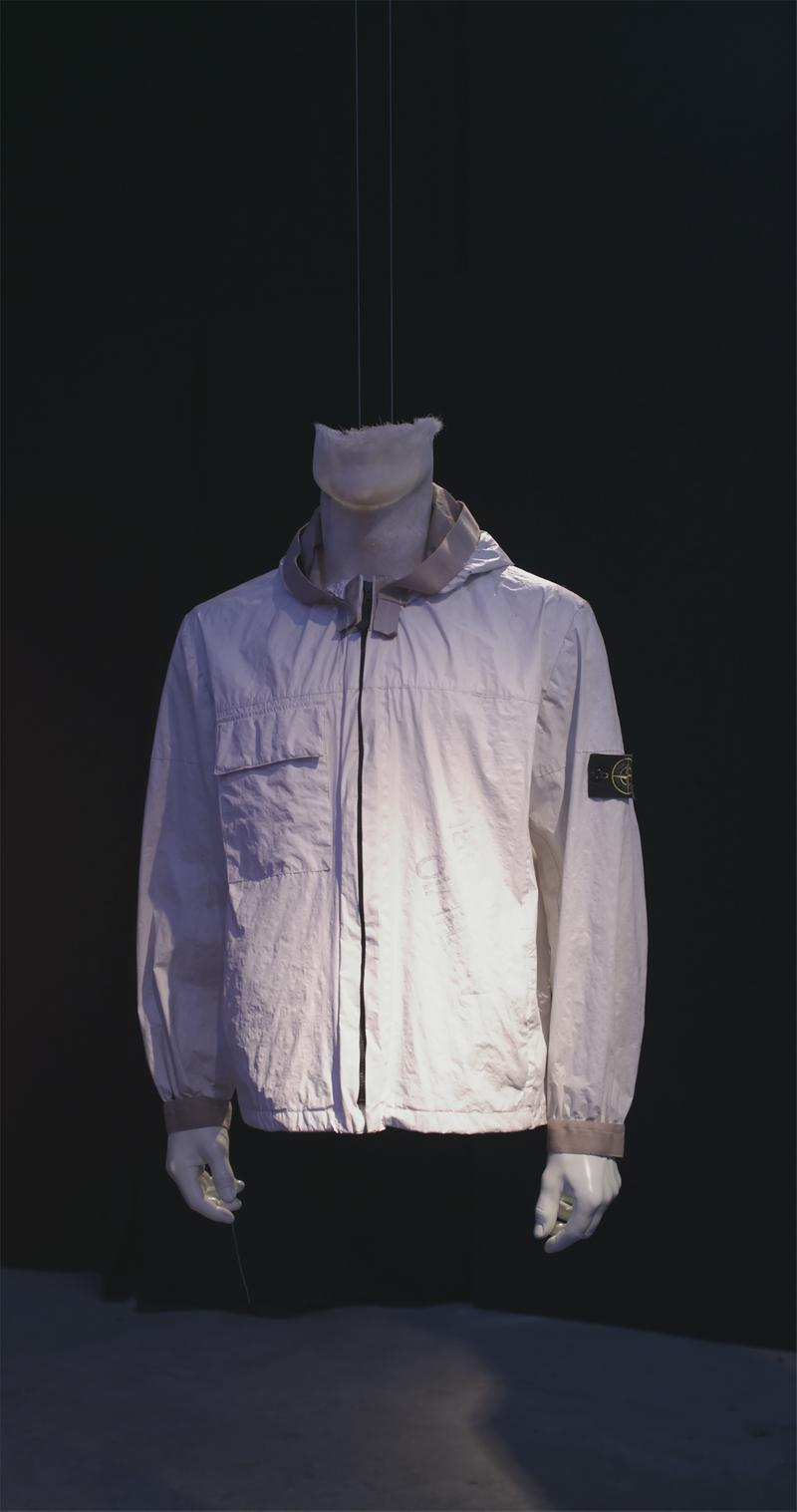 White zip up jacket with contrasting trim on the collar and cuffs and Stone Island badge on the upper left sleeve displayed on mannequin bust