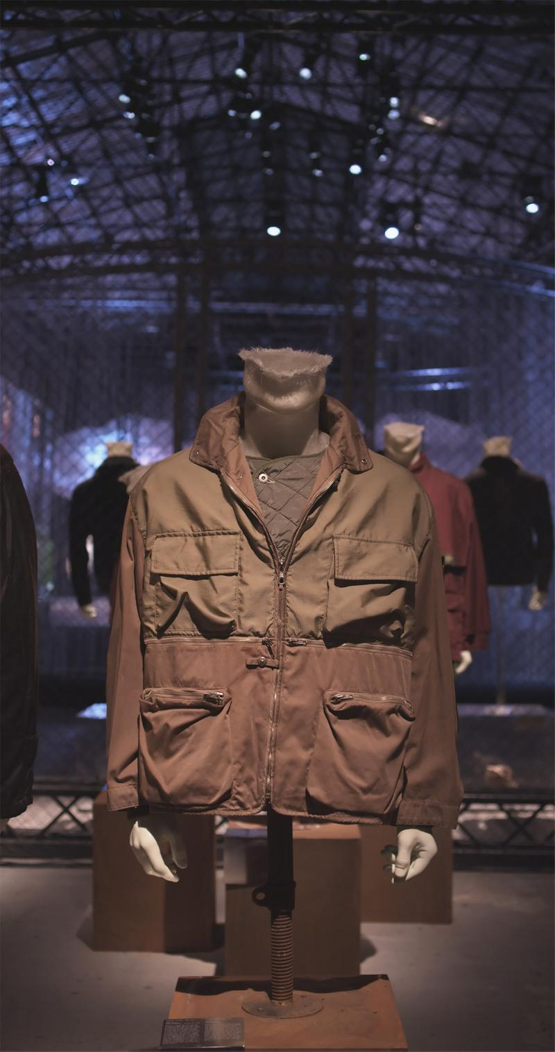 Two toned brown multi pocket jacket with zipper closure and high collar displayed on mannequin bust in exhibition hall