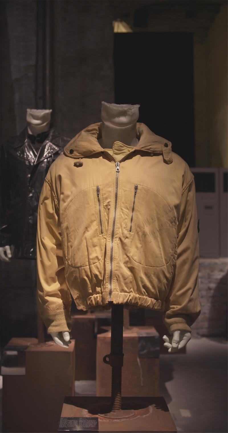 Mustard zippered jacket with wide collar displayed on mannequin bust