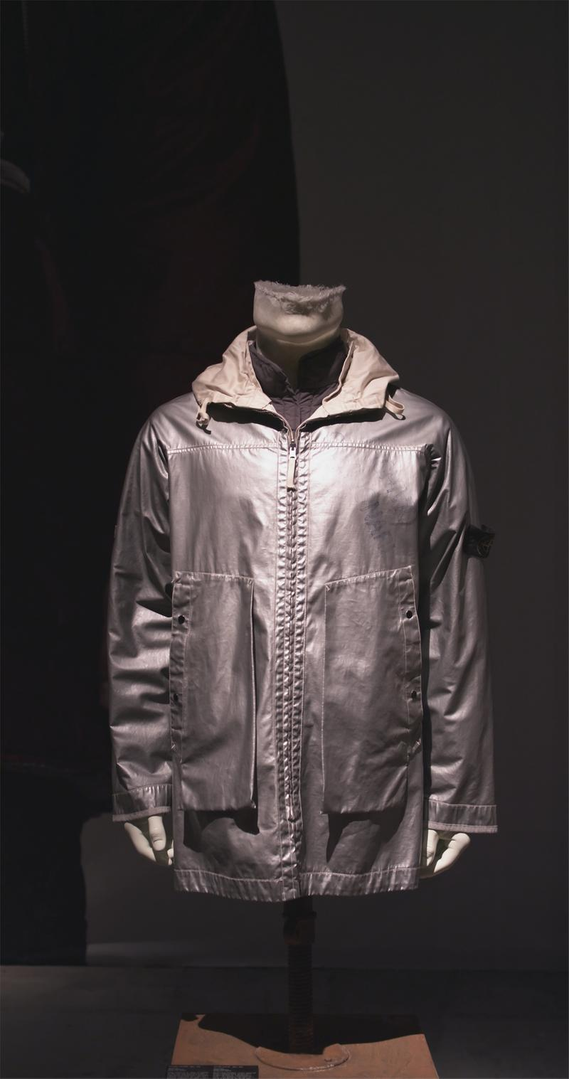 Shiny silver long hooded zip up jacket with side pockets, off white lining and Stone Island badge on left sleeve displayed on mannequin bust