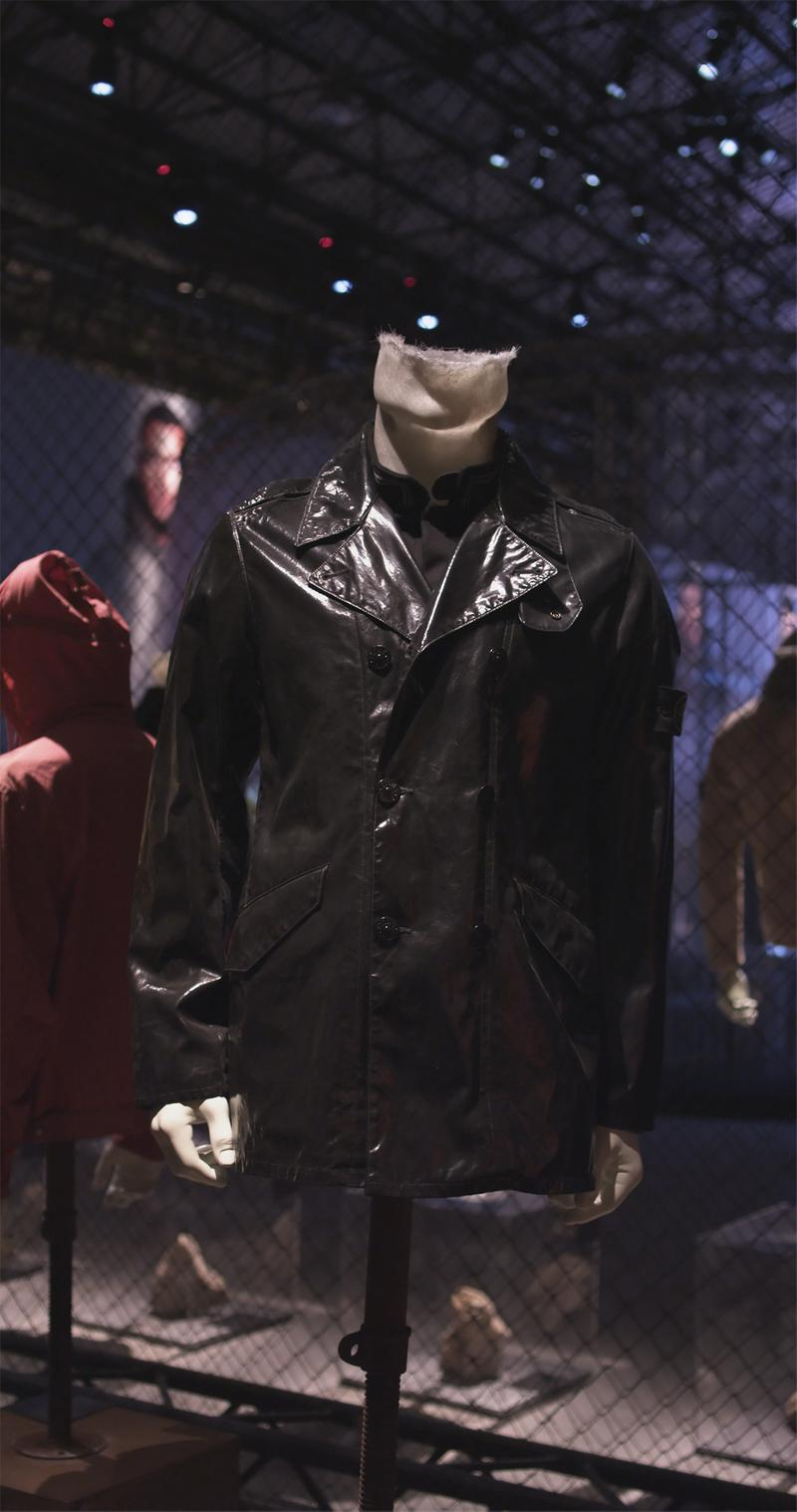 High shine black buttoned jacket with wide collar displayed on mannequin bust against chain link fence