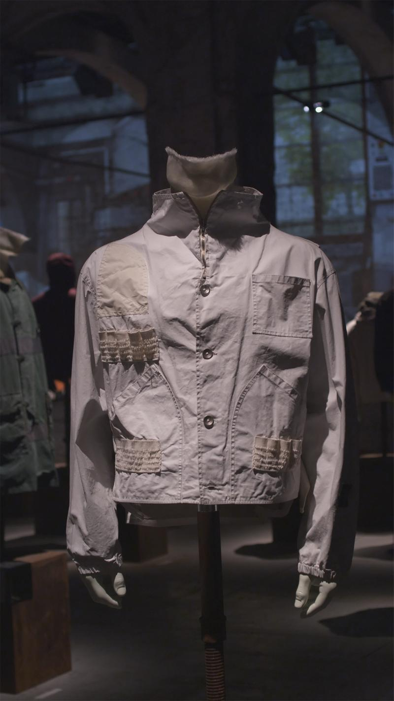 Light gray jacket with light tan panel accents, buttoned closure, and patch pockets displayed on mannequin bust