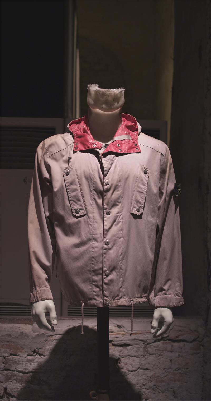 Gray hooded jacket with red lining, button closure, snap buttons detail oat chest and Stone Island badge on upper left sleeve displayed on mannequin bust