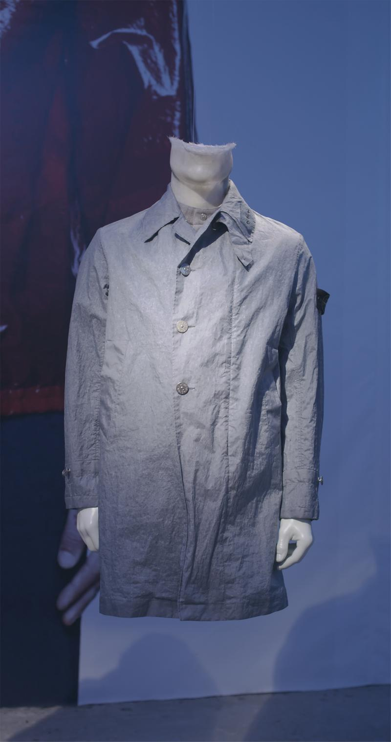 Gray shirt collar jacket with button closure and Stone Island badge on upper left sleeve displayed on mannequin bust