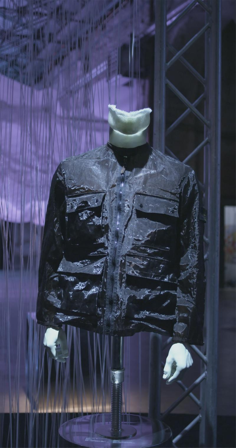 Dark colored, shiny jacket with no collar, zipper closure and four buttoned flap pockets, displayed on mannequin bust