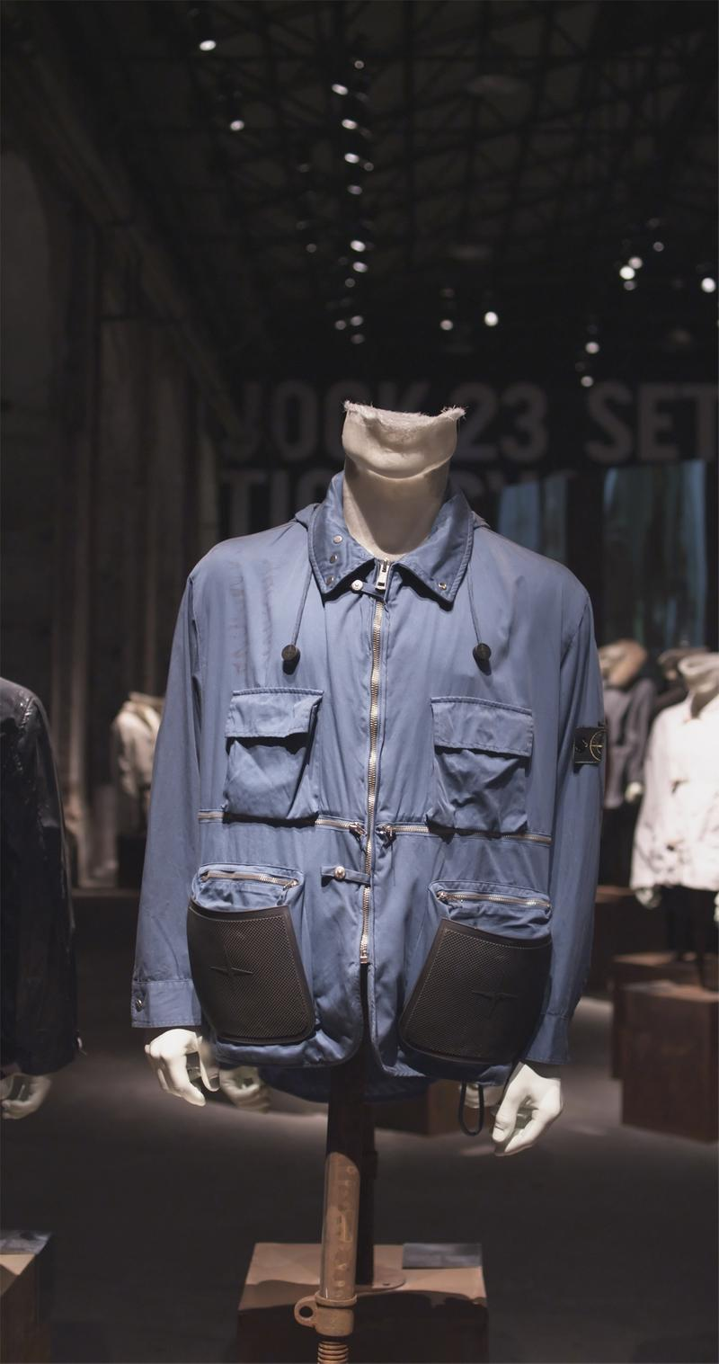 Blue zippered jacket with drawstring collar, zippered pockets, patch pockets, and Stone Island badge on upper left sleeve displayed on mannequin bust