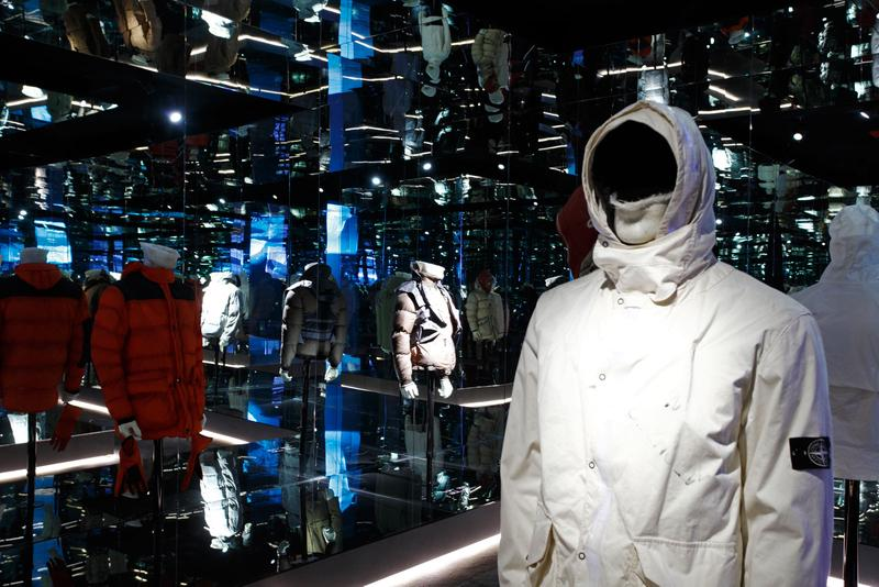 White hooded parka with white button closure and flap pockets on chest, displayed on mannequin bust in mirror paneled room with other jackets on display in the background