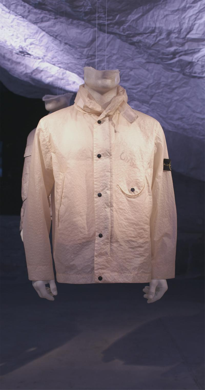 Light beige button up jacket with high collar, buttoned pocket on the left and Stone Island badge on upper left sleeve displayed on mannequin bust
