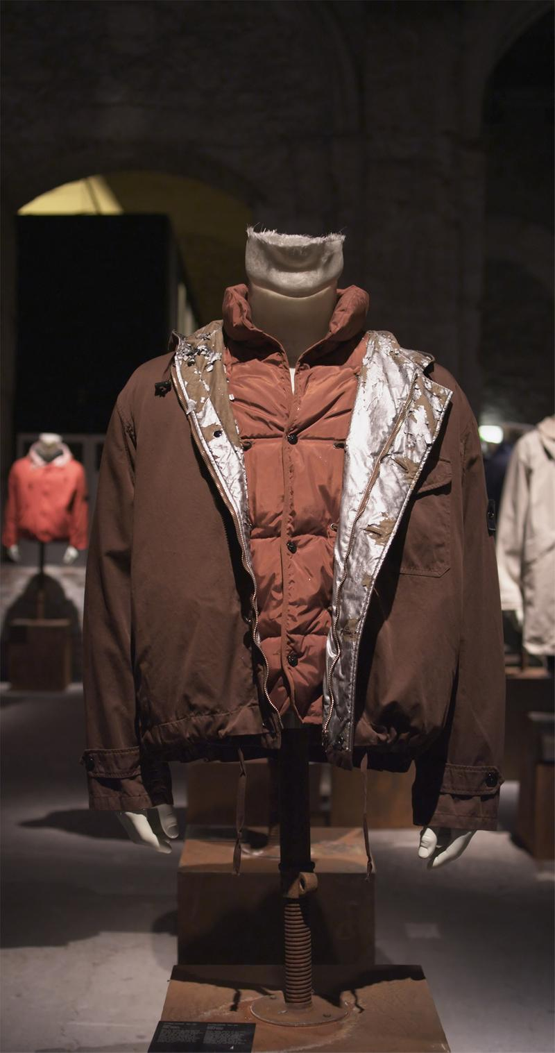 Brown zippered jacket with silver lining over buttoned dark red puffer jacket displayed on mannequin bust