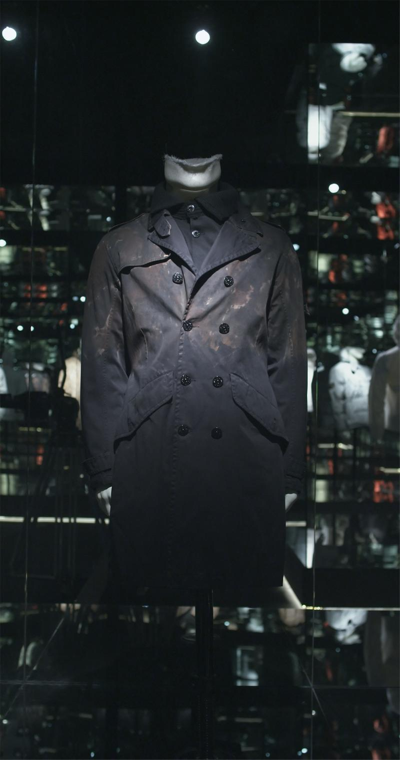 Dark colored double breasted long jacket with flap collar and flap pockets displayed on mannequin bust