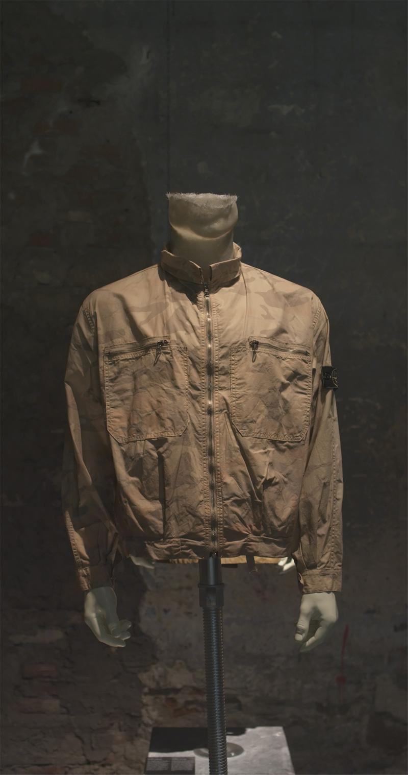 Light brown zip up jacket with stand collar, zippered chest pockets and Stone Island badge on the upper left sleeve, displayed on a mannequin bust