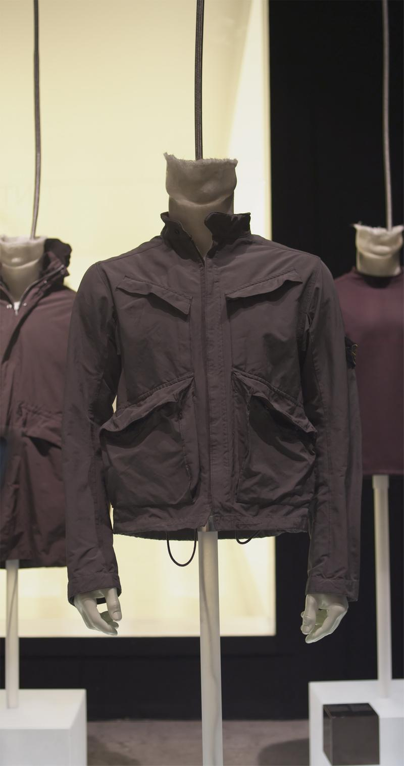 Dark colored jacket with zipper closure and four flap pockets, displayed on a mannequin bust