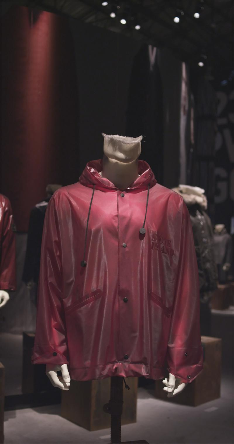 Red parka with hood and button closure displayed on mannequin bust
