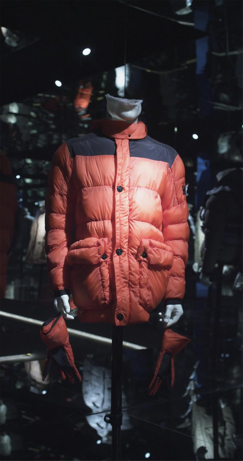 Bright red puffer jacket with front pockets, contrasting black shoulder panels and black buttons, displayed on mannequin bust