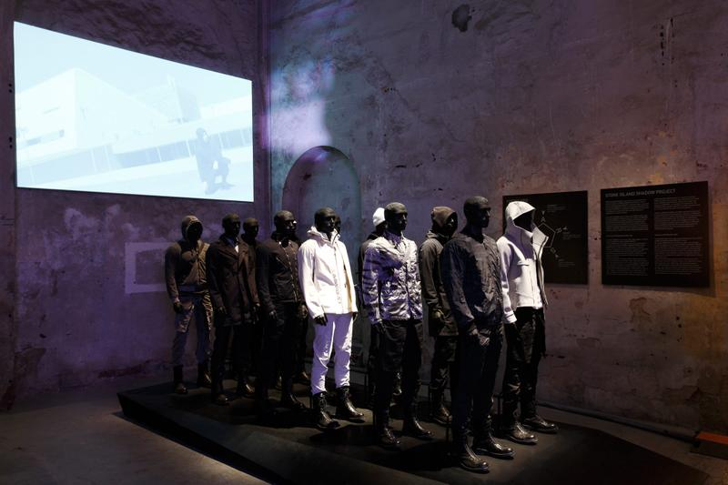 Mannequins displaying various jackets and pants in dark interior with a screen in the background