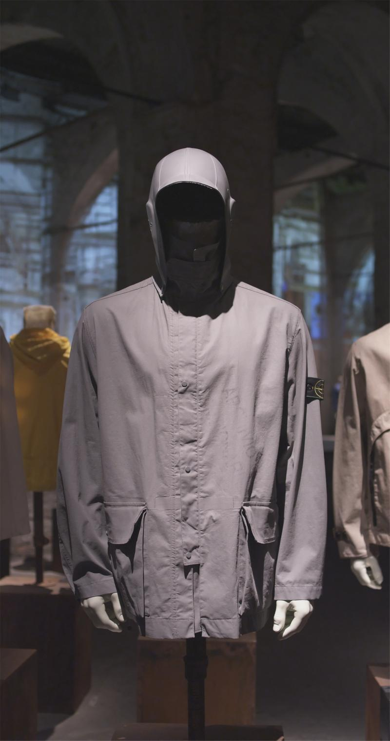 Hooded gray jacket displayed on mannequin bust with flap pockets on sides and Stone Island badge on upper left sleeve