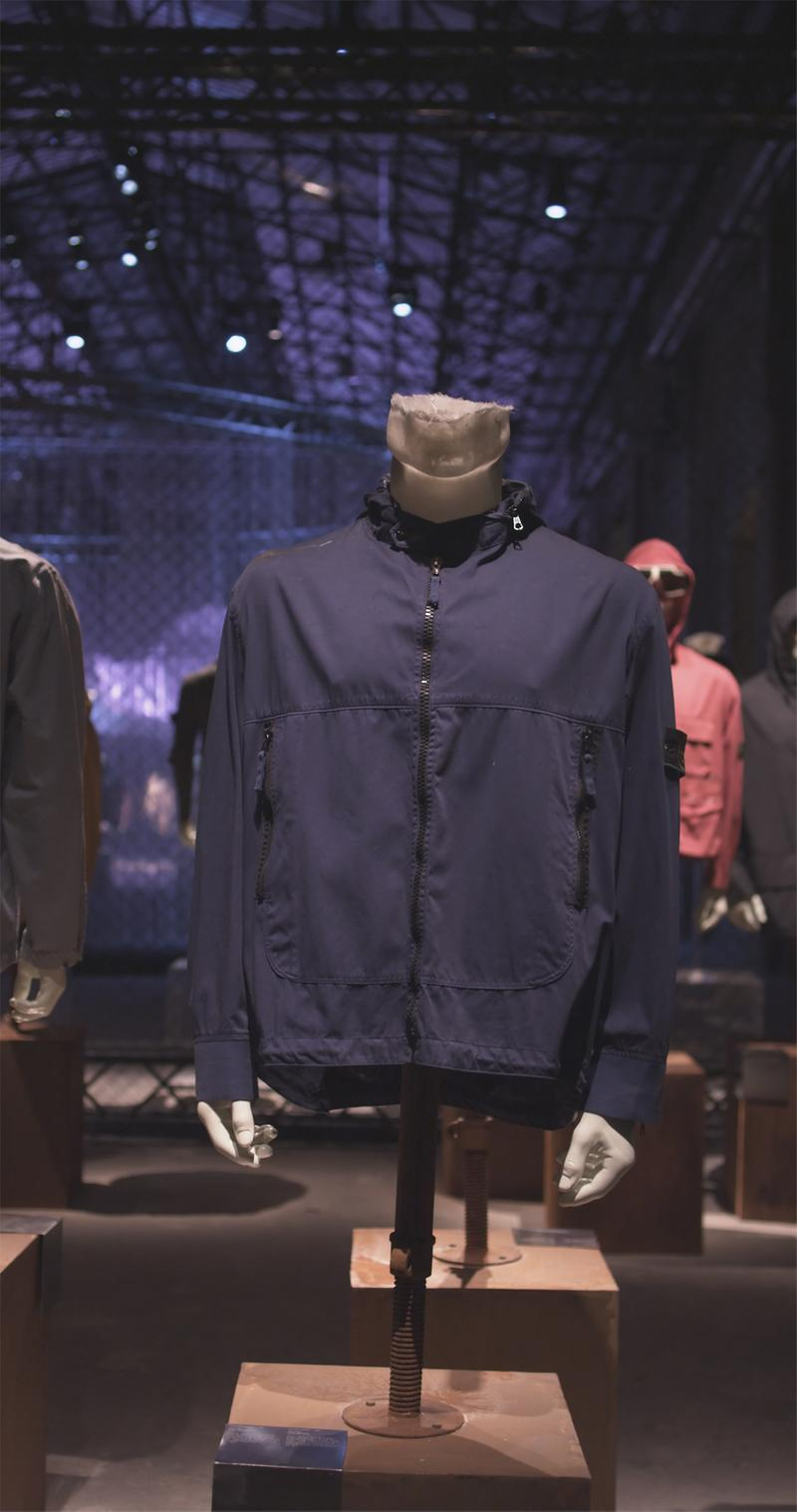 Dark blue zippered jacket with high collar and pockets with zipper closure, displayed on mannequin bust in exhibition hall