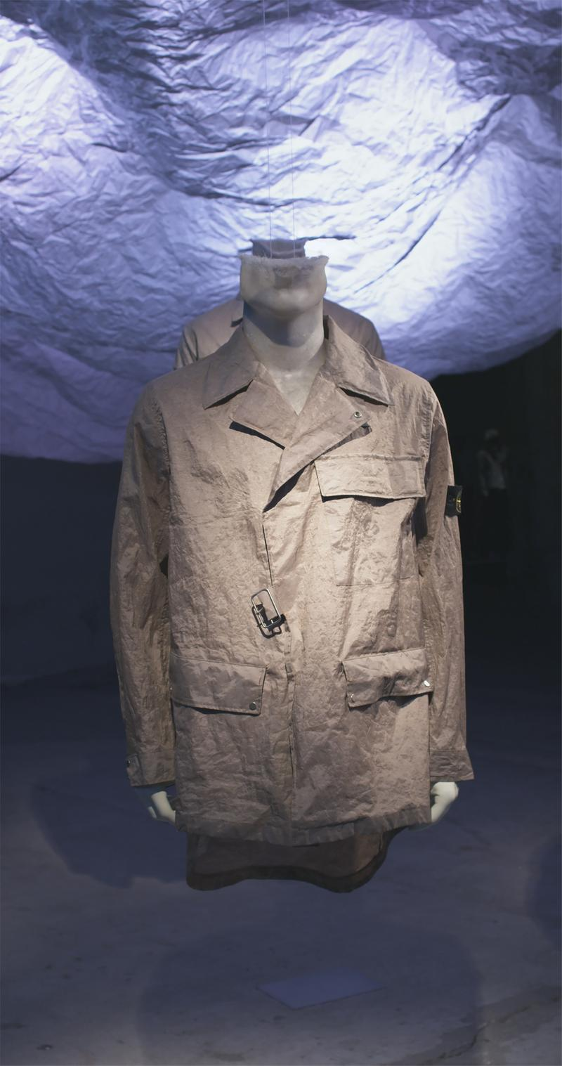 Khaki jacket with notched collar, three flap pockets, and Stone Island badge on upper left sleeve displayed on mannequin bust