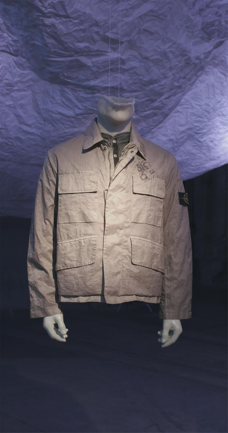 Tan shirt collar jacket with four patch pockets and faded lettering on left chest, displayed on mannequin bust