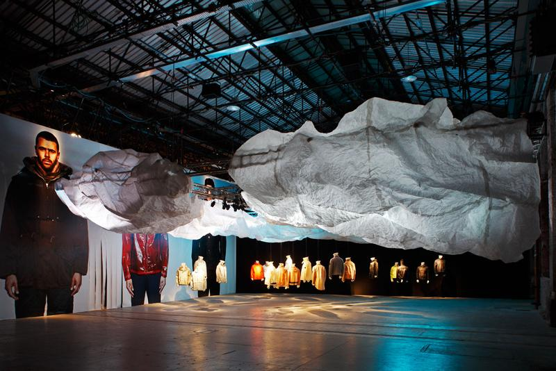 Exhibition hall with model photo mural, cloud structure, and various jackets on display