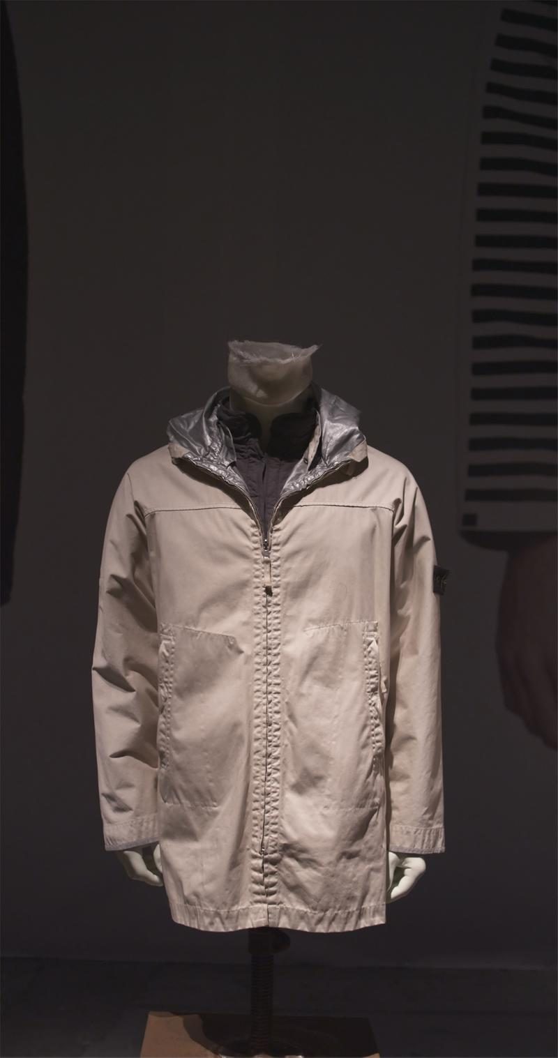 Off white long zip up jacket with side pockets, silver lining and Stone Island badge on left sleeve displayed on mannequin bust