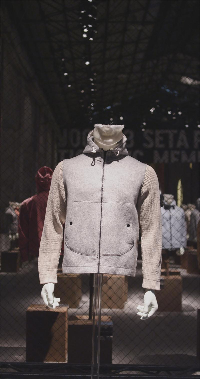 Gray zip up sweater with high drawstring collar and contrasting sleeves displayed on mannequin bust