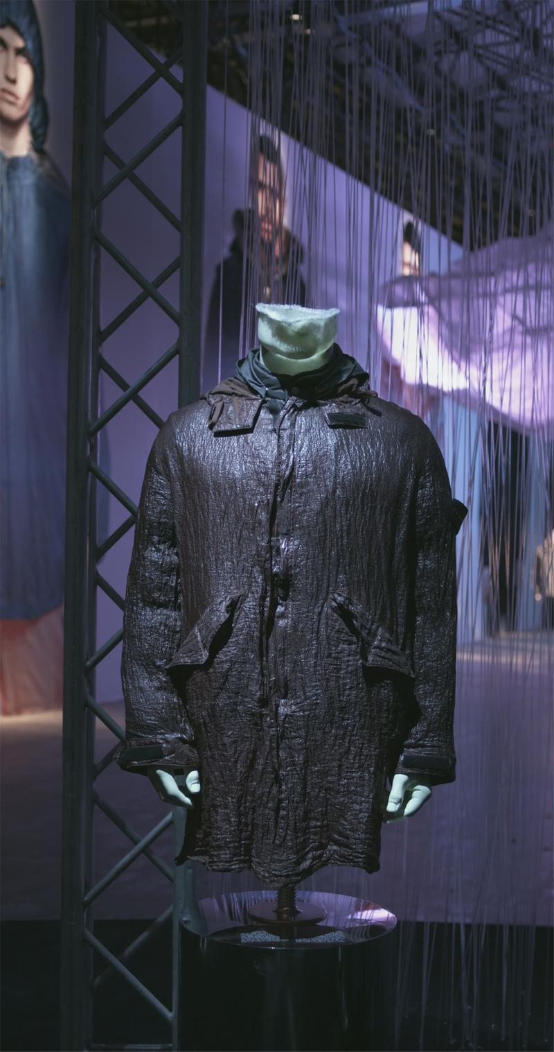 Long black shiny parka with side pockets and front closure, displayed on mannequin bust