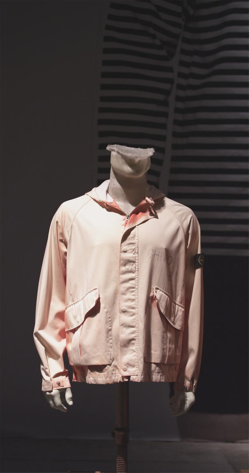 Light peach zip up jacket with side flap pockets, faded lettering on left chest and Stone Island badge on left sleeve displayed on mannequin bust