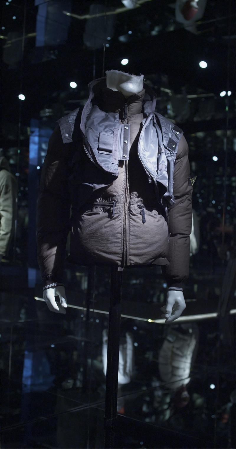 Multilayered dark zip-up puffer jacket with snap button details and pockets with zipper closure, displayed on a mannequin bust