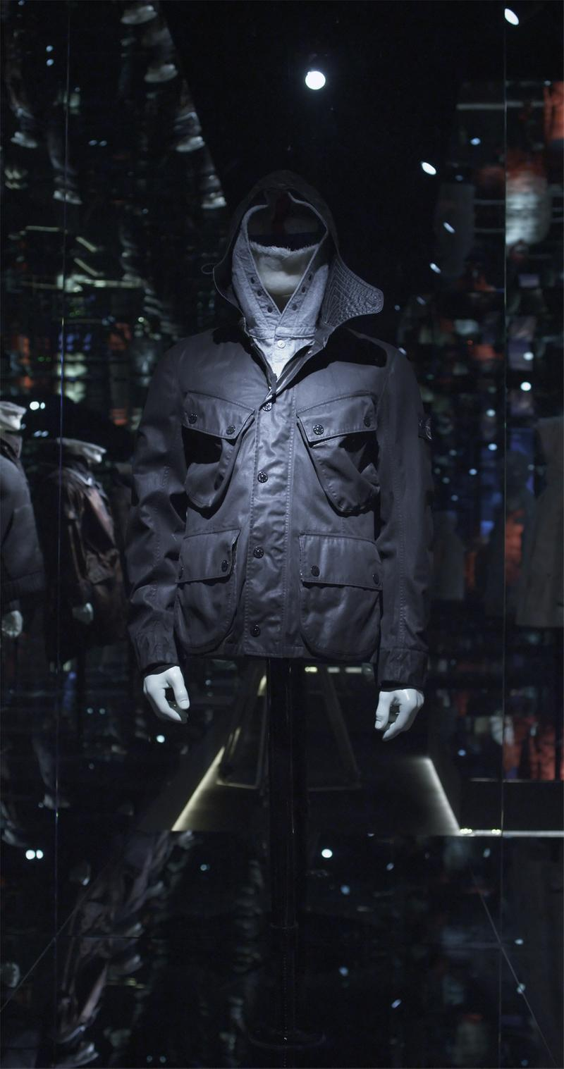 Black zip up jacket with stand collar and four patch pockets displayed on mannequin bust