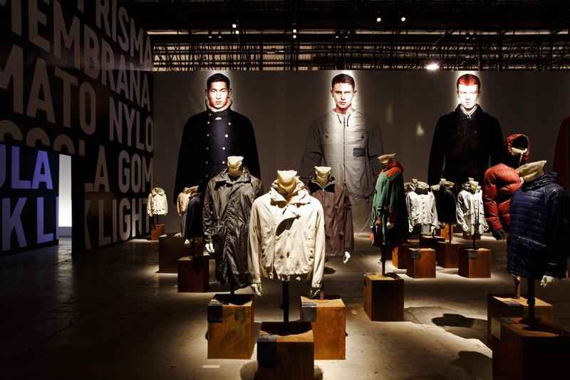 Exhibition hall with model photo mural in the background, word mural on the left and many jackets on display on mannequin busts