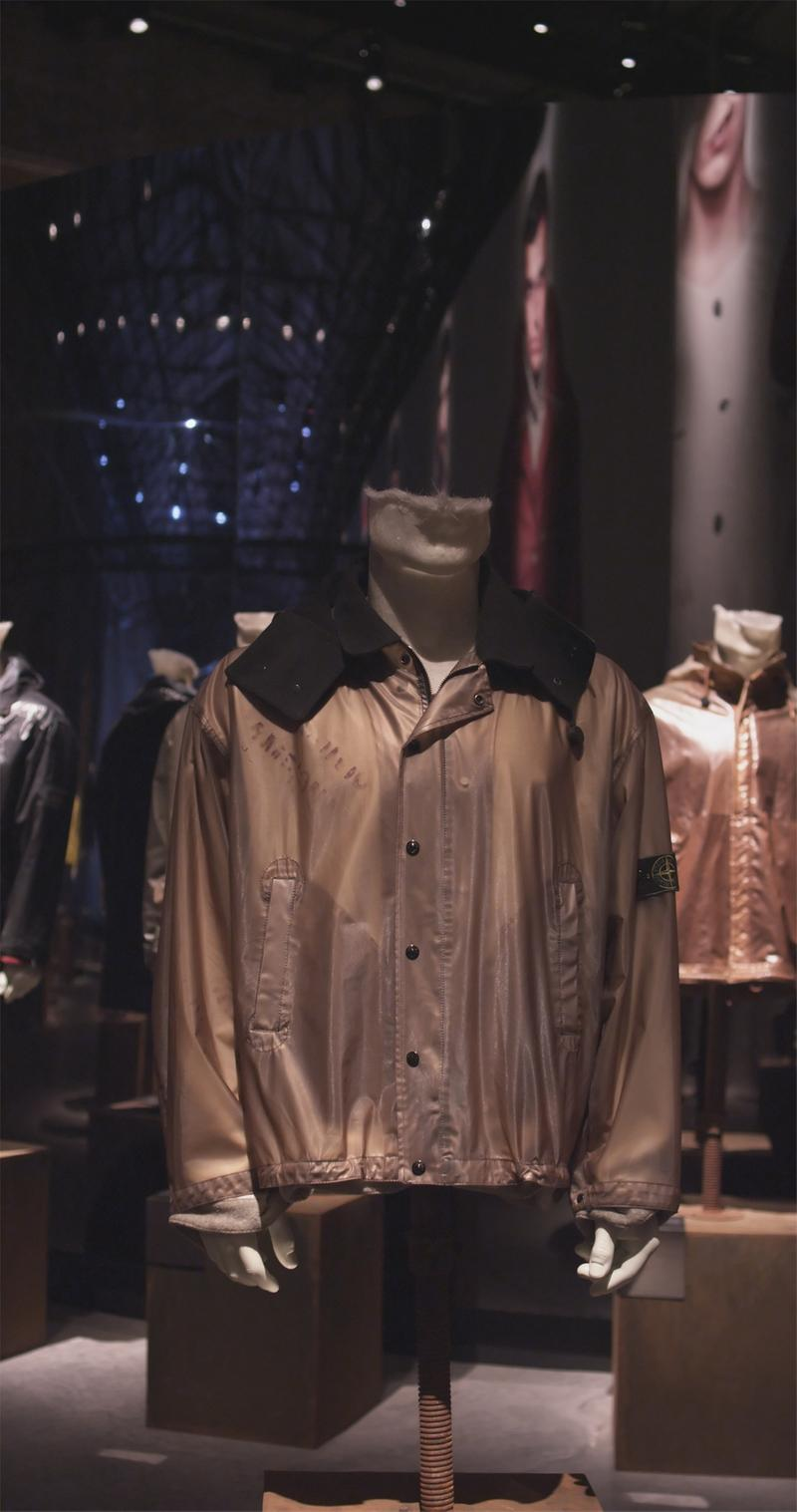 Brown draped jacket with wide collar, button closure and faded lettering at right chest, displayed on mannequin bust