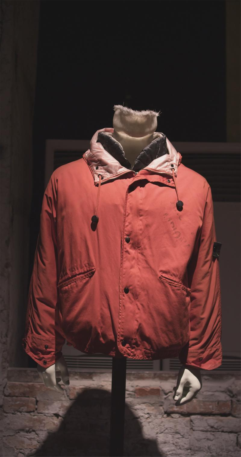 Red jacket with drawstrings, button closure, and faded lettering on left chest, displayed on mannequin bust