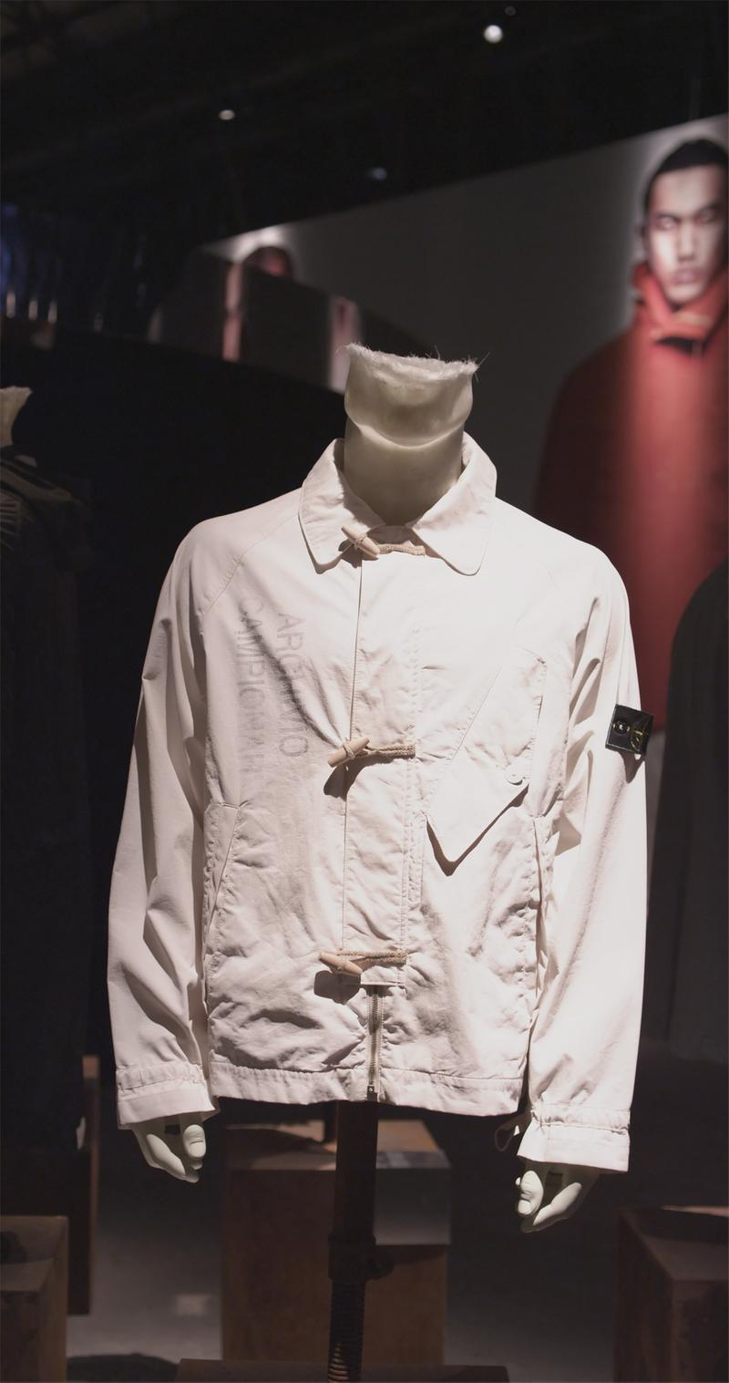 Off white jacket displayed on mannequin bust with toggle closures, collar, side pockets, Stone Island badge on upper left sleeve and faded lettering on the chest