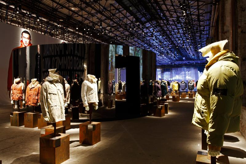 Exhibition hall with model photo mural on the left and many jackets on display on mannequin busts