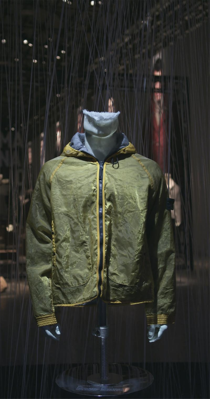 Green hooded jacket with contrasting yellow trim around edges and yellow sleeve cuffs, displayed on mannequin bust