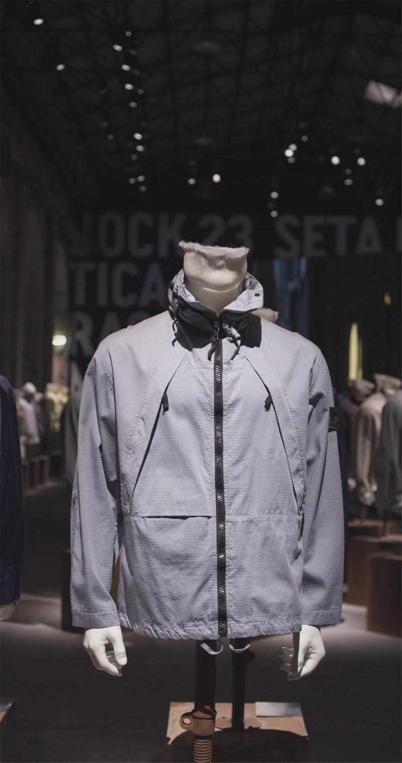 Gray zippered jacket with high collar and diagonal chest pockets with zipper closure, displayed on mannequin bust