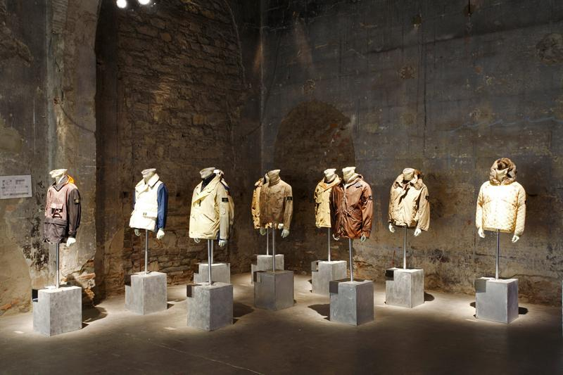 Various jackets of different colors and styles displayed on mannequin busts mounted on concrete blocks