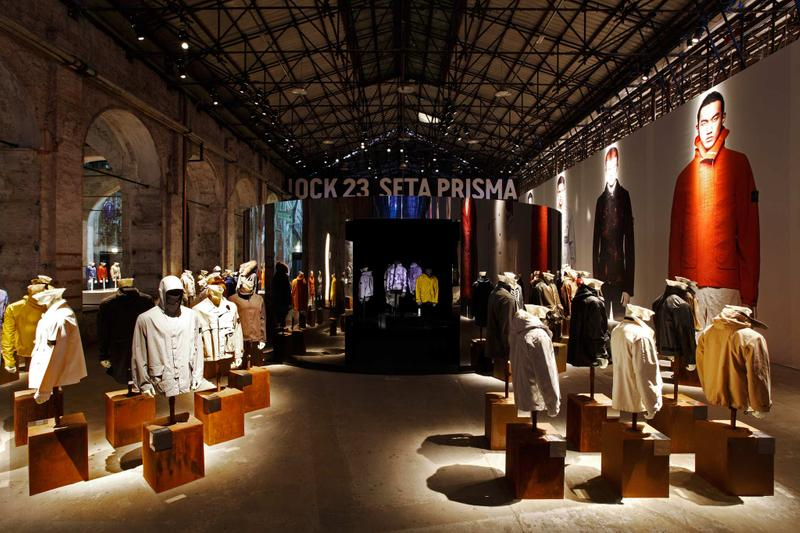 Various jackets in different styles and shades displayed on mannequin busts in exhibition hall with model photos on the right wall