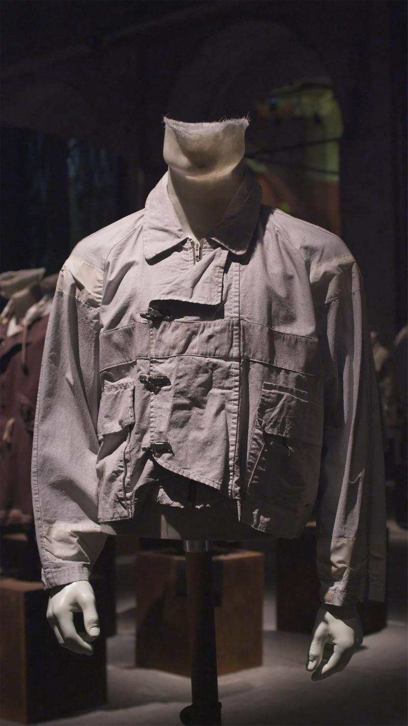 Gray jacket with asymmetrical toggle closure and flap pockets, displayed on mannequin bust