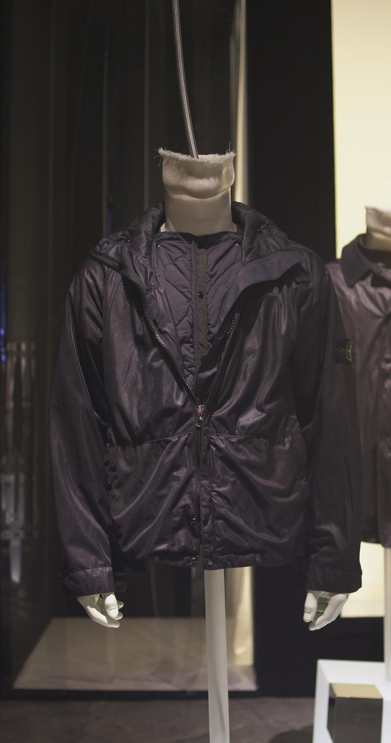 Shiny black zip up jacket with cinched waist on a mannequin bust styled over a quilted layer of the same color