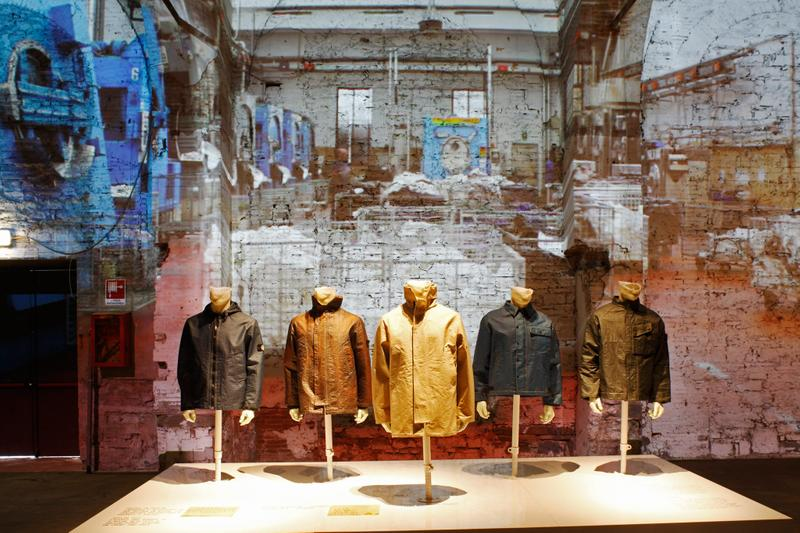 Several jackets of various colors and styles displayed on mannequin busts in against a distressed, painted brick background with projected images
