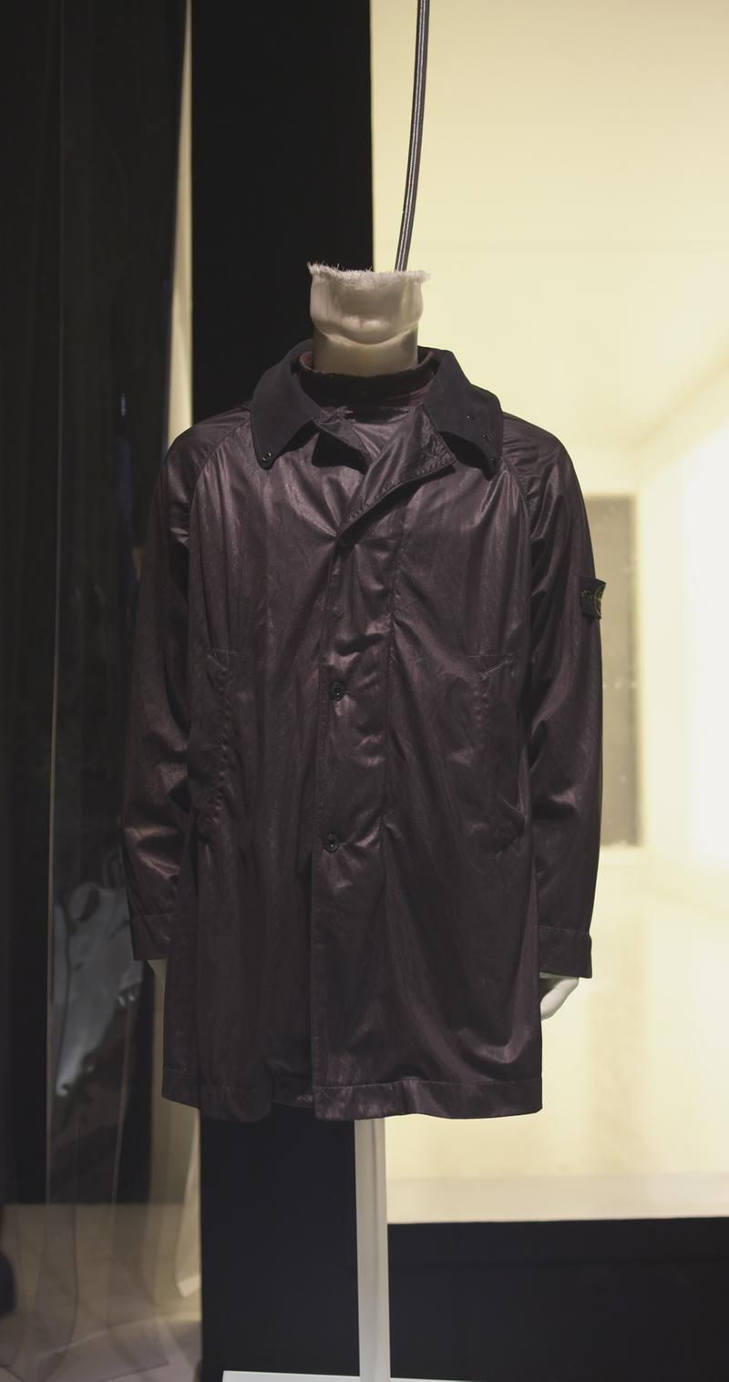 Long black jacket with button closure, wide collar and side pockets, displayed on a mannequin bust