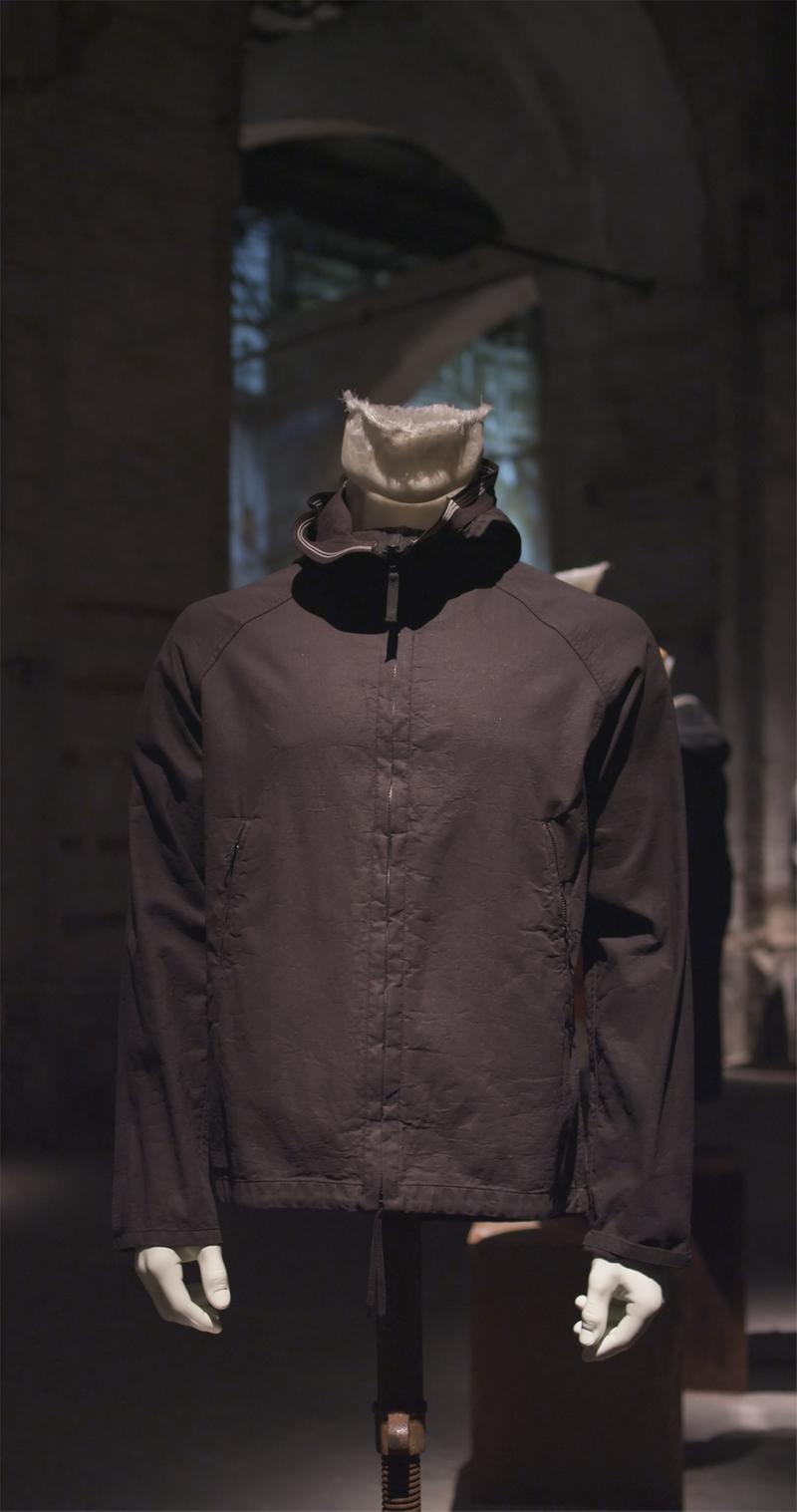 Dark jacket with high collar and zipper down the front displayed on mannequin bust