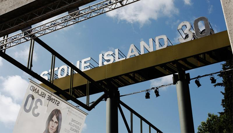 STONE ISLAND 30 photo banner against blue sky in front of concrete structure
