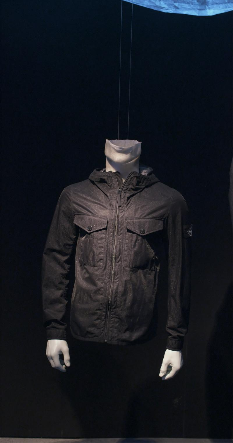 Black zip up jacket with flap pockets on the chest and hood displayed on mannequin bust