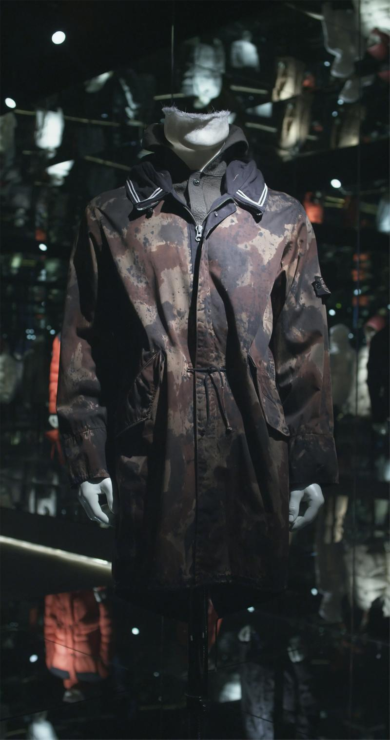 Zip up mid length camouflage print jacket with cinched waist, black collar with white stripes and side pockets displayed on mannequin bust